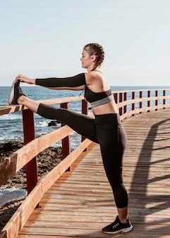 Vista laterale della donna atletica che si estende all'aperto sulla spiaggia