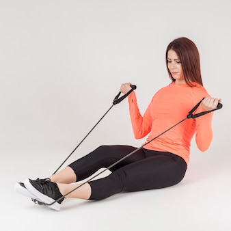 Side view of athletic woman using the resistance band