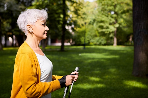 Vista laterale della donna in pensione atletica attraente con taglio di capelli grigio pixie godendo di nordic walking utilizzando bastoncini speciali, facendo esercizio fisico cardio in una bella giornata autunnale in campagna. età e stile di vita
