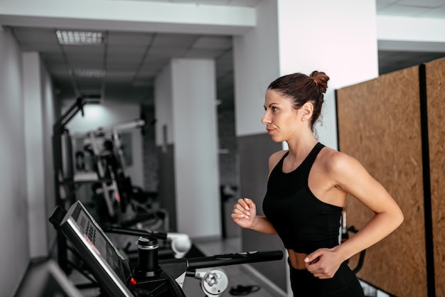 Side view of attractive sports woman running on treadmill.