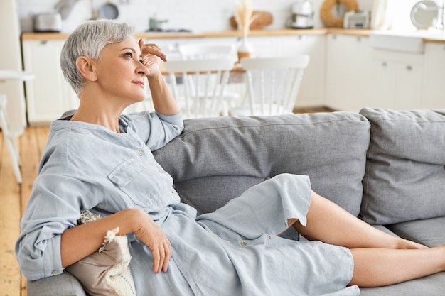 Side view of attractive stylish european female pensioner in elegant dress sitting barefooted on comfortable couch, having thoughtful look, daydreaming. people, retirement, mature age and lifestyle