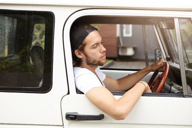 Side view of attractive young bearded hipster sitting on driver's seat while driving his white jeep with his elbow hanging down of open window on sunny day while going to barbecue with his friends