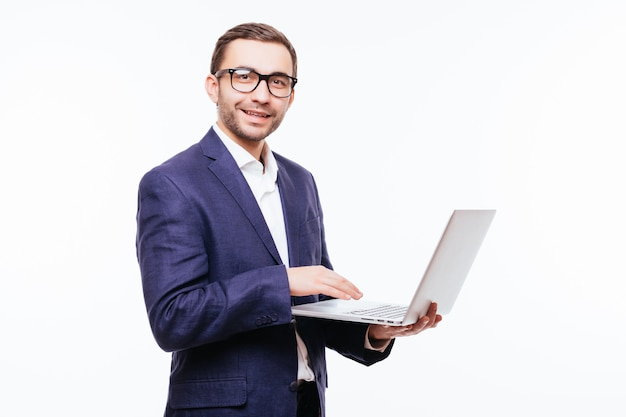 Side view of attractive young businessman in classical suit using laptop, standing against white wall