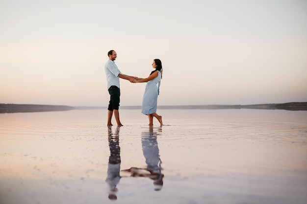 Vista laterale di una giovane coppia attraente che si tiene per mano e in piedi sulla spiaggia