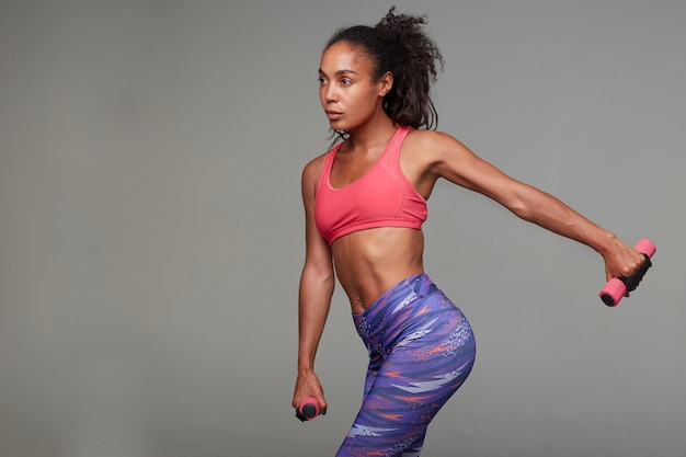 Side view of attractive young dark haired curly lady with ponytail hairstyle putting her hand aside while holding weighting agents, standing in colored sporty wear