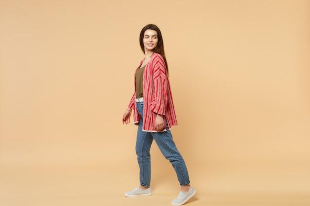 Vista laterale della giovane donna attraente in abiti casual in piedi e guardando da parte isolato su sfondo muro beige pastello in studio. concetto di stile di vita di emozioni sincere della gente. mock up copia spazio.