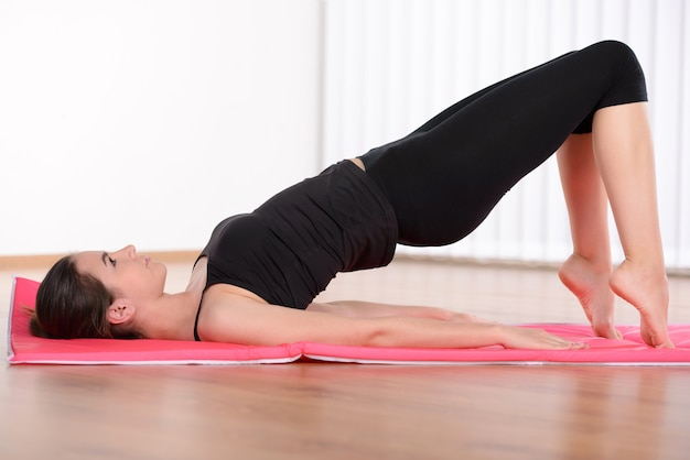 Side view of attractive young woman training on yoga mat.