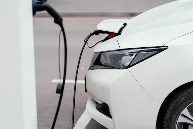 Side view of automobile being charged at electric vehicle charging station