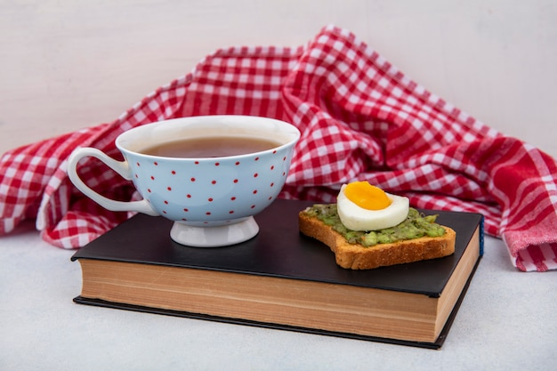 Side view of avocado on a bread with poached egg and a cup of tea over book on red checked tablecloth and white surface