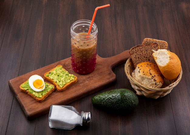 Side view of avocado pulps on toasted bread slices with egg on a wooden kitchen board with juice in a glass with a bucket of breads on wooden surface