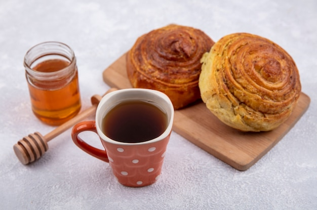 Side view of azerbaijani traditional pastry gogal on a wooden kitchen board with a cup of tea and honey on a glass jar on a white background