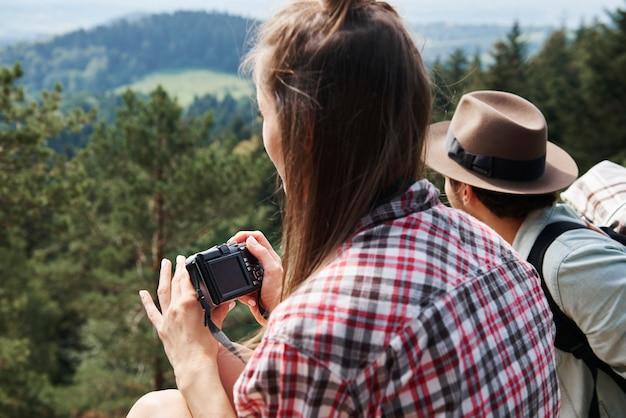 Vista laterale del viaggiatore con zaino e sacco a pelo che utilizza la fotocamera in montagna