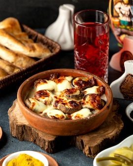 Side view of baked mushrooms with cheese in a clay bowl