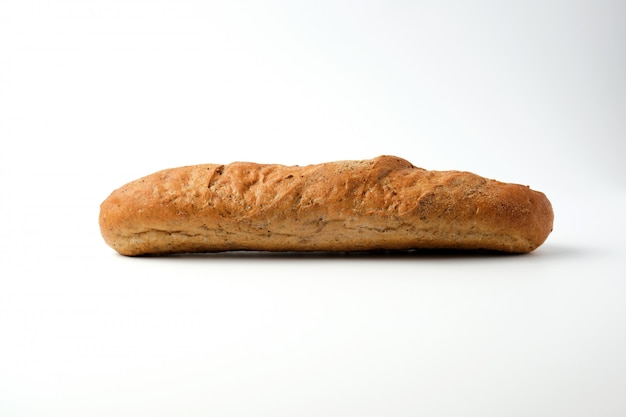 Side view of a baked rye flour baguette on a white