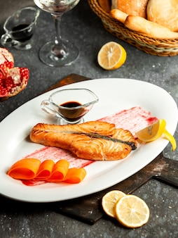 Side view of baked salmon served with narsharab pomegranate sauce and lemon on white plate