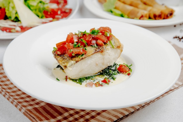 Side view of baked seabass with tomatoes