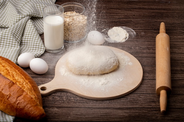 Side view of baking concept with dough and flour on cutting board with rolling pin eggs milk baguette on wooden background