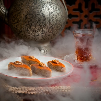 Side view baklava with glass of tea and iron ancient teapot in white plate in dark smoked