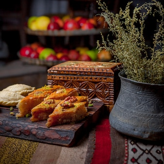Side view baklava with shekerbura and casket and antique copper dishes in wooden plank