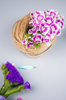 Side view of a ball of rope with purple color turkish carnation and statice flowers on white table