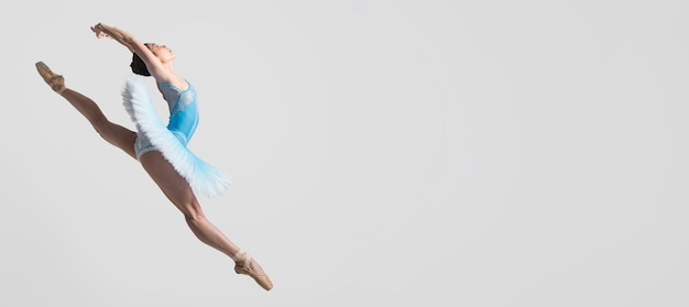 Side view of ballerina in the air with copy space