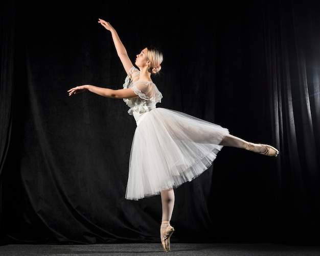 Side view of ballerina dancing in tutu dress