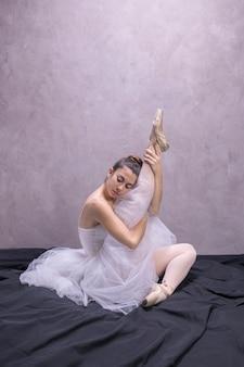 Side view ballerina holding her leg up