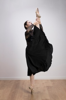 Side view ballerina holding up her leg