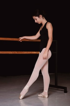 Side view of ballerina in leotard and pointe shoes