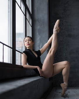 Side view of ballerina in leotard posing with leg up