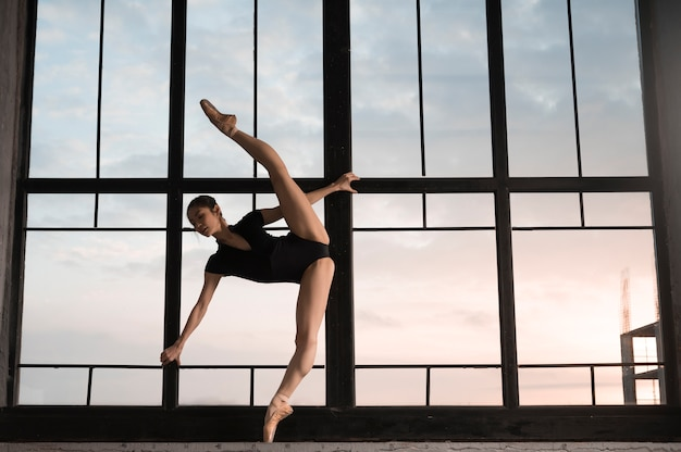 Side view of ballerina in leotard stretching