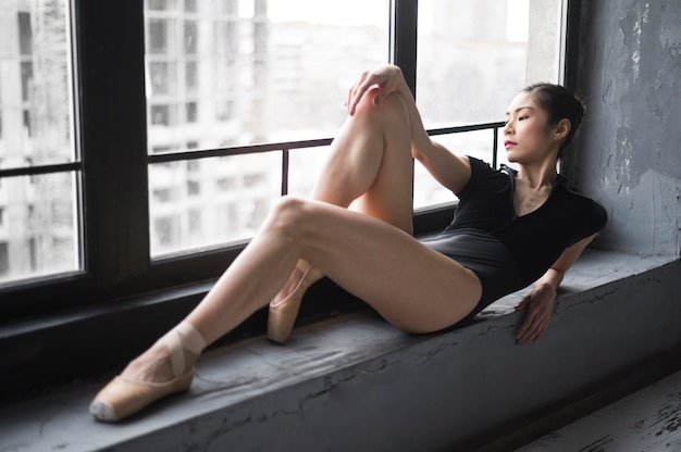 Side view of ballerina posing by the window in leotard