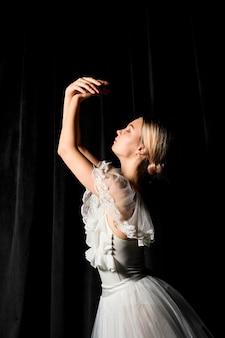 Vista laterale della ballerina in posa in abito tutu con le braccia in alto
