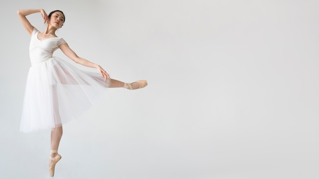 Side view of ballerina posing in tutu dress with copy space