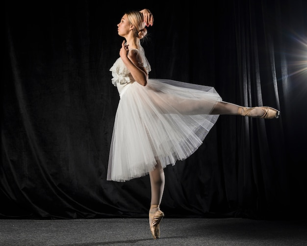 Side view of ballerina posing in tutu dress