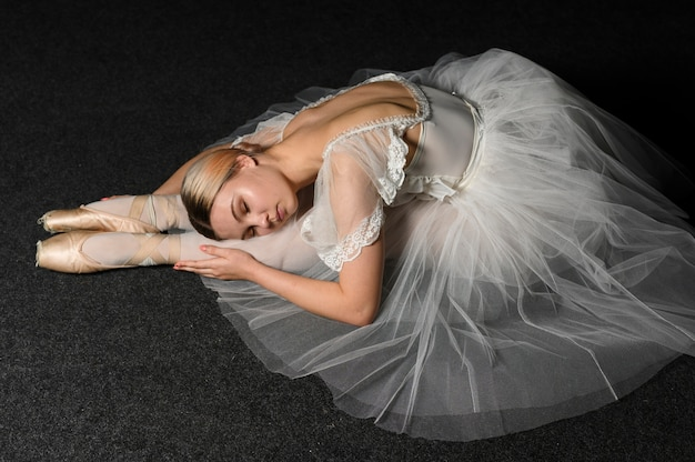 Side view of ballerina in tutu dress stretching
