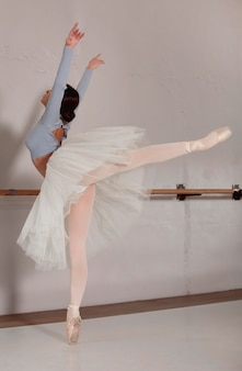 Side view of ballerina in tutu skirt dancing