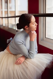 Side view of ballerina in tutu skirt looking through the window