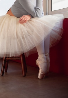 Side view of ballerina in tutu skirt and pointe shoes next to window