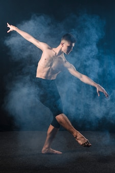 Side view of ballerino dancing in tights with smoke