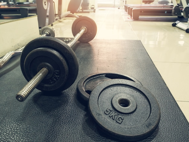 Side view of barbell on the floor in fitness gym