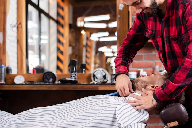 Side view barber grooming a beard