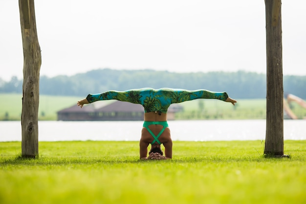 Side view of barefoot young concentrated woman doing handstand in park in summer day