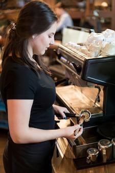 Barista vista laterale con macchina per il caffè