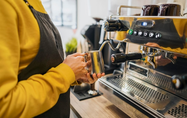 Side view of barista using machine