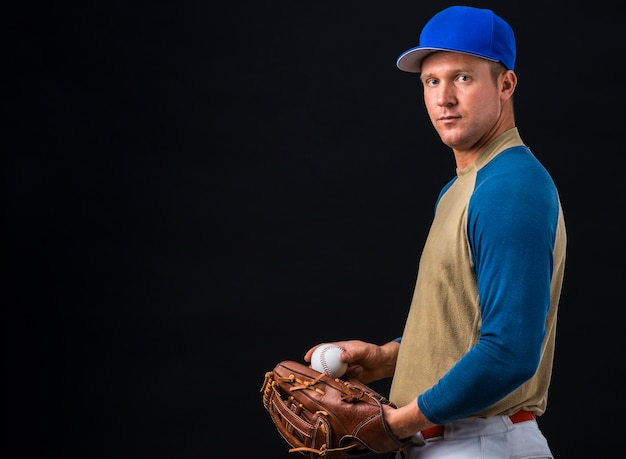 Side view of baseball player posing with ball and glove