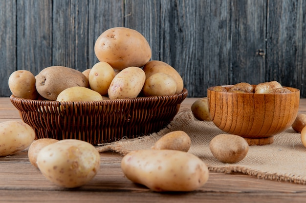 Side view of basket and bowl full of potato on sackcloth on wooden surface and background with copy space