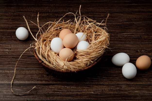 Side view of basket of eggs in nest with eggs around on wooden background