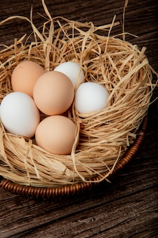 Side view of basket of eggs in nest on wooden background