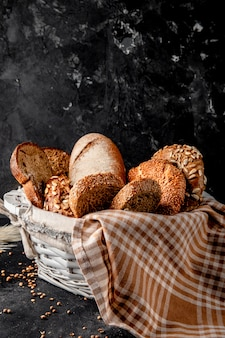 Side view of basket full of breads as bagel baguette rye on black surface and black surface